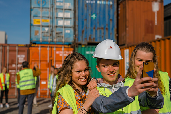 kids doing a selfie in front of containers